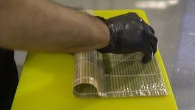 Manos del cocinero que preparan la comida japonesa, cocinero que hace el sushi, preparando el rollo de sushi almacen de metraje de vídeo