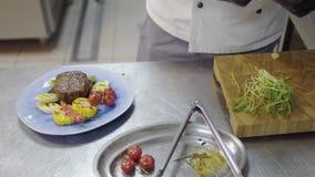 Manos del cocinero del restaurante que adornan el plato asado a la parrilla delicioso del filete, del maíz, de la hierba de limón almacen de video