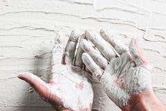 Manos del constructor en yeso blanco mojado en la pared del estuco Imagen de archivo