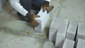Manos del constructor que toman el bloque de cemento aireado y que lo ponen en la fundación del cemento almacen de video