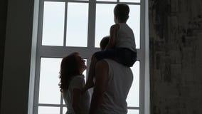 Manos del control de los padres El hijo se sienta en los hombros del ` s del padre Siluetas de la familia en una ventana La famil almacen de video