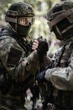 Manos del control de los soldados en bosque Imagen de archivo