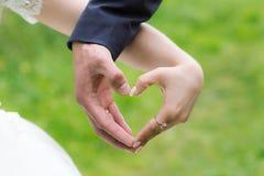 Manos del corazón de la boda imagenes de archivo