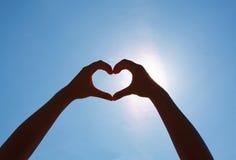Manos del corazón de las muchachas en el cielo Imagen de archivo libre de regalías
