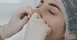 Manos del cosmetologist que da masajes a los labios del paciente después del aumento del labio Cierre para arriba almacen de metraje de vídeo