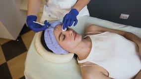Manos del Cosmetologist que hacen la inyección de la belleza para la mujer caucásica joven metrajes