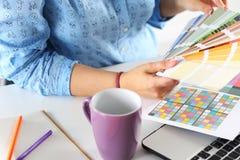 Manos del diseñador de sexo femenino en la oficina que trabaja con las muestras del color Fotografía de archivo libre de regalías