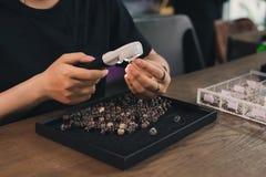 Manos del diseñador de sexo femenino de la joyería que mira su trabajo con el magnif imagen de archivo
