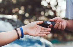 Manos del distribuidor autorizado profesional que dan llave de sistemas del coche fotografía de archivo