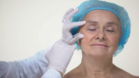 Manos del doctor que hacen las inyecciones faciales para envejecer al paciente femenino, dermatología almacen de video