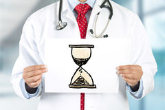 Manos del doctor que llevan a cabo la muestra con el reloj de la arena Foto de archivo