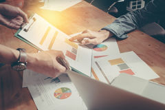 Manos del equipo del negocio en el trabajo con plan financiero y en de madera foto de archivo