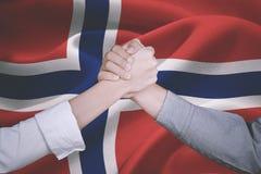 Manos del equipo del negocio con la bandera noruega Fotografía de archivo