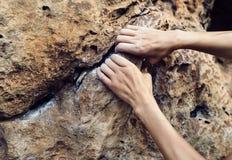 Manos del escalador que suben en el borde del acantilado fotos de archivo libres de regalías
