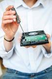 Manos del especialista de las TIC que sostienen HDD con destornillador Imágenes de archivo libres de regalías