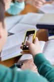 Manos del estudiante con el smartphone que hace la chuleta Imágenes de archivo libres de regalías