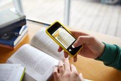 Manos del estudiante con el smartphone que hace la chuleta Imagen de archivo
