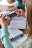 Manos del estudiante con el smartphone que hace la chuleta Fotos de archivo libres de regalías