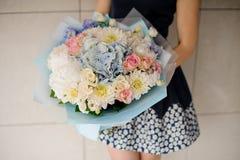 Manos del florista con el ramo floral colorido hermoso Fotografía de archivo libre de regalías