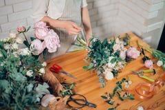 Manos del florista contra la mesa con las herramientas y las cintas de funcionamiento en el fondo de madera Fotografía de archivo libre de regalías