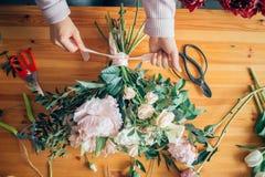 Manos del florista contra la mesa con las herramientas y las cintas de funcionamiento en la tabla de madera Fotografía de archivo libre de regalías