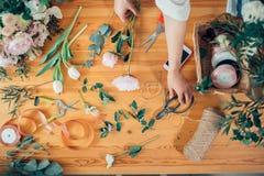 Manos del florista contra la mesa con las herramientas y las cintas de funcionamiento en la tabla de madera Imagenes de archivo