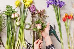 Manos del florista que hacen que el ramo salta flores Foto de archivo
