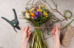 Manos del florista que hacen que el ramo salta flores Fotografía de archivo