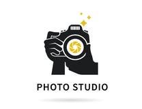 Manos del fotógrafo con el ejemplo plano de la cámara para el icono o la plantilla del logotipo Imágenes de archivo libres de regalías