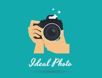 Manos del fotógrafo con el ejemplo plano de la cámara para el icono o la plantilla del logotipo Fotos de archivo libres de regalías