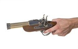 Manos del fragmento con una pistola vieja Imagen de archivo libre de regalías