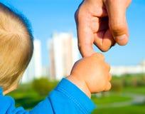 Manos del hijo y del padre del niño Fotografía de archivo libre de regalías