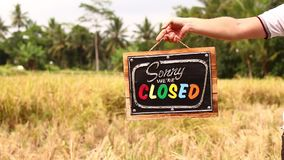 Manos del hombre con el tablero cerrado de la muestra en un fondo tropical de la naturaleza Isla de Bali almacen de metraje de vídeo
