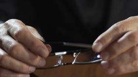 Manos del hombre de negocios adulto que sostienen las lentes y que las ponen en la tabla, abogado almacen de metraje de vídeo