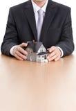 Manos del hombre de negocios alrededor del modelo arquitectónico casero Imagenes de archivo