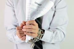 Manos del hombre de negocios con las cadenas y el contrato Imágenes de archivo libres de regalías