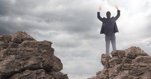 Manos del hombre de negocios en aire en rocas contra las nubes con la llamarada imágenes de archivo libres de regalías