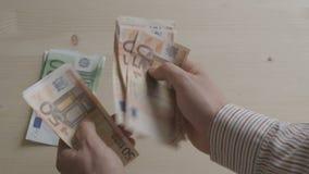 Manos del hombre de negocios que cuentan la opinión superior de las cuentas euro metrajes