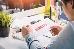 Manos del hombre de negocios que llevan a cabo la letra de rechazo en la mesa en el hom Imágenes de archivo libres de regalías