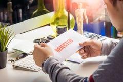 Manos del hombre de negocios que llevan a cabo la letra de rechazo en la mesa en el hom Fotografía de archivo libre de regalías