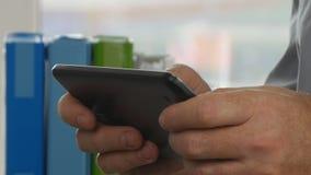 Manos del hombre de negocios que mandan un SMS usando la conexión inalámbrica electrónica de la tableta en oficina almacen de metraje de vídeo