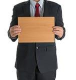 Manos del hombre de negocios que muestran al tablero en blanco de madera Imagenes de archivo
