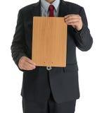 Manos del hombre de negocios que muestran al tablero en blanco de madera Foto de archivo libre de regalías