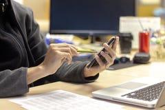 Manos del hombre de negocios que sostienen el lápiz y el smartphone con los comp del ordenador portátil foto de archivo libre de regalías