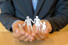 Manos del hombre de negocios que sostienen el papel de la familia Concepto de la atención sanitaria y del seguro imagenes de archivo