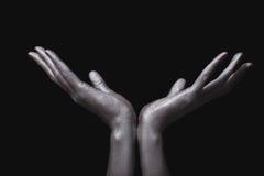 Manos del hombre hermoso en la pintura de plata Imagen de archivo