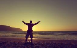 Manos del hombre joven para arriba en una playa en la puesta del sol Fotografía de archivo