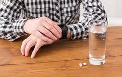 Manos del hombre mayor con el vidrio de agua y de píldoras Foto de archivo