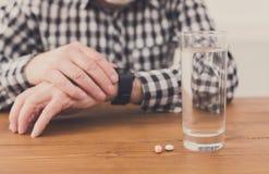 Manos del hombre mayor con el vidrio de agua y de píldoras Imagen de archivo libre de regalías