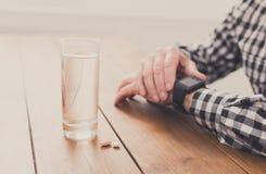 Manos del hombre mayor con el vidrio de agua y de píldoras Imagenes de archivo